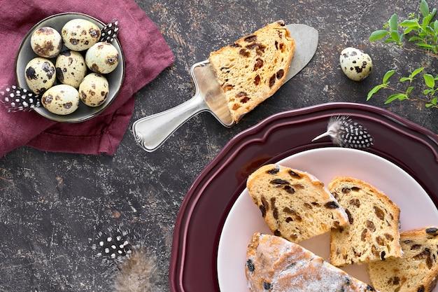 Paasbrood (osterbrot in het duits). bovenaanzicht van traditionele fruitige brood op donkere tafel met verse bladeren en kwarteleitjes Premium Foto