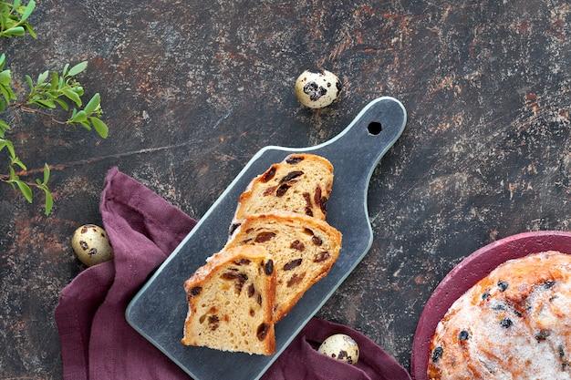Paasbrood (osterbrot in het duits). hoogste mening van traditioneel fruitig brood op donkere lijst met verse bladeren en kwartelseieren Premium Foto