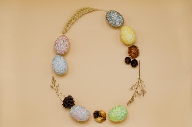 Paasei-vorm met kleurrijke beschilderde eieren van kleurpotlood versieren met droge bladeren en bloemen. Premium Foto