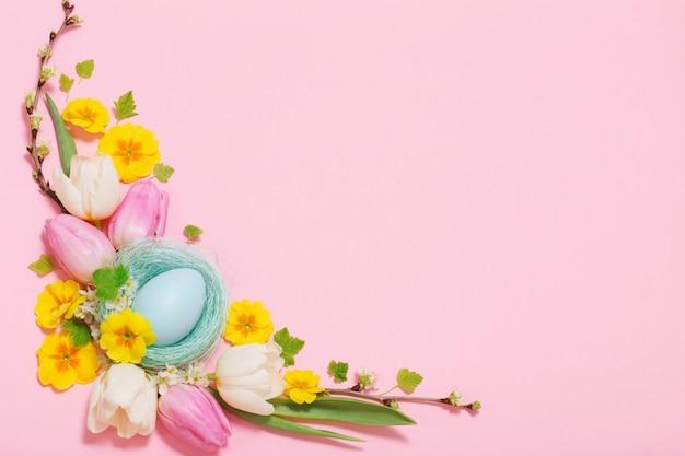 Paaseieren en lentebloemen op roze achtergrond Premium Foto