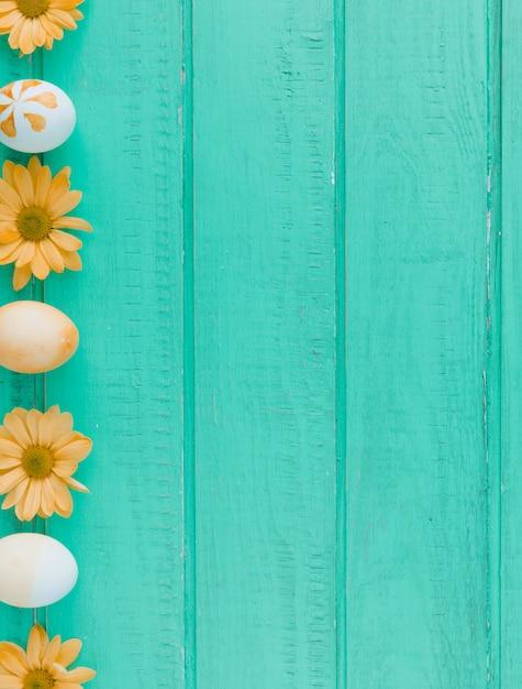 Paaseieren en oranje bloemen op bureau Gratis Foto