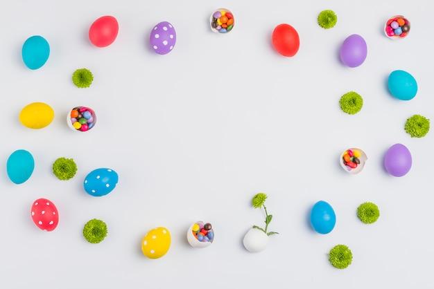 Paaseieren met snoepjes en bloemen verspreid op witte tafel Gratis Foto