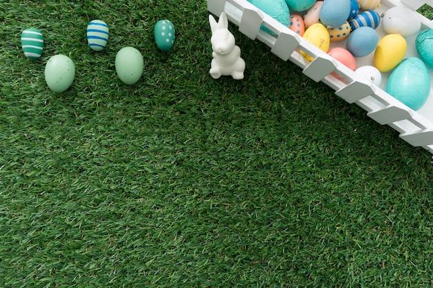 Paashaas en gekleurde eieren op grasmat Gratis Foto