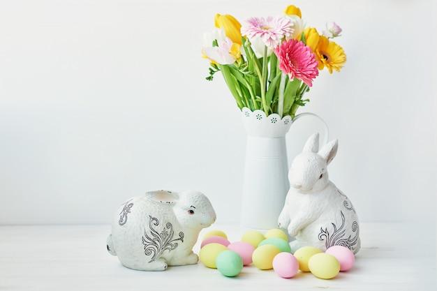 Paashaas en paaseieren op keukenlijst. witte konijnzitting op lijst met boeket van tulpen en rand en kleurrijke eieren. Premium Foto