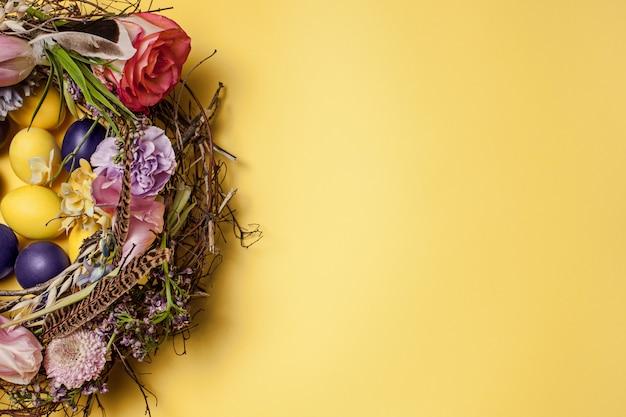 Paaskaart. geschilderde paaseieren in nest op geel Gratis Foto