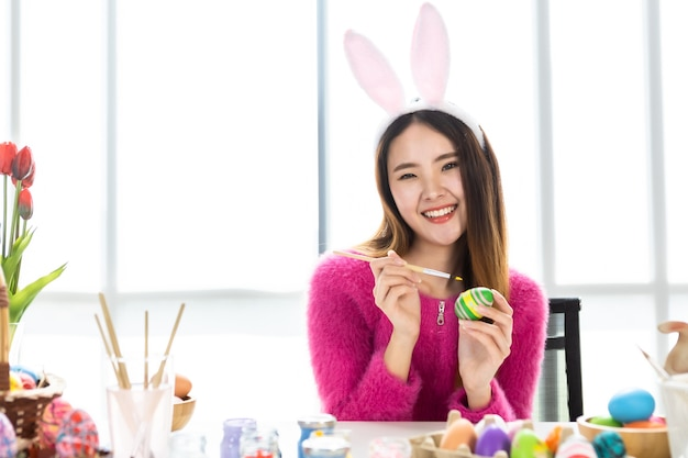 Paasvakantie concept, happy aziatische jonge vrouw draagt bunny oren hand beschilderde eieren voor pasen met kleurrijke paaseieren in de witte kamer achtergrond Premium Foto