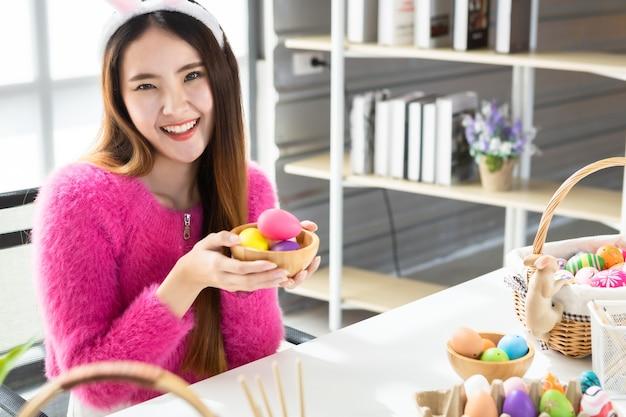Paasvakantie concept, happy aziatische jonge vrouw show met een mand met kleurrijke paaseieren in de witte kamer achtergrond Premium Foto