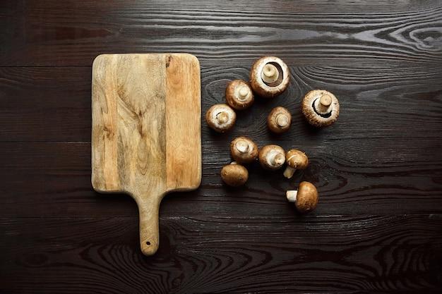 Paddestoelen en snijplank, groep van verse bruine champignons verspreid over een houten achtergrond, bovenaanzicht, platte lat. ongekookt voedselingrediënt Premium Foto