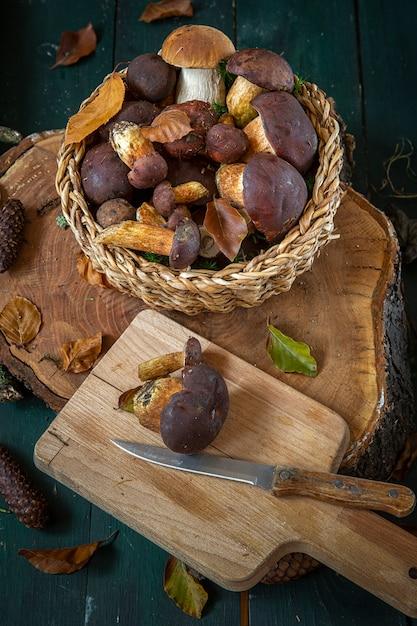 Paddestoelen in een mand op een snijplank met een mes. seizoensgebonden paddestoelen plukken. voorbereidingen voor de winter, zelfgemaakte marinades maken. bos in de herfst. eetbare paddestoel. herfst Premium Foto