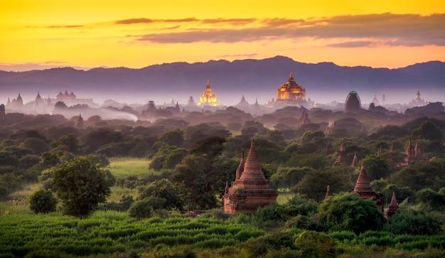 Pagodelandschap onder een warme zonsondergang bij schemering in de vlakte van bagan, myanmar. Premium Foto