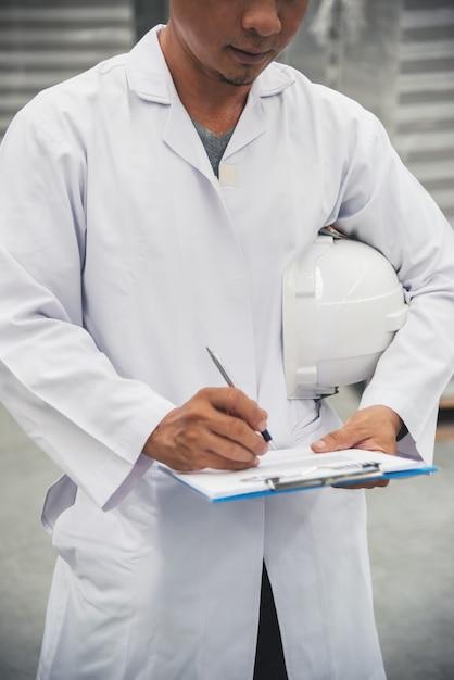 Pakhuisarbeider die zijn lijst controleert op klembord in een grote pakhuisfabriek Premium Foto