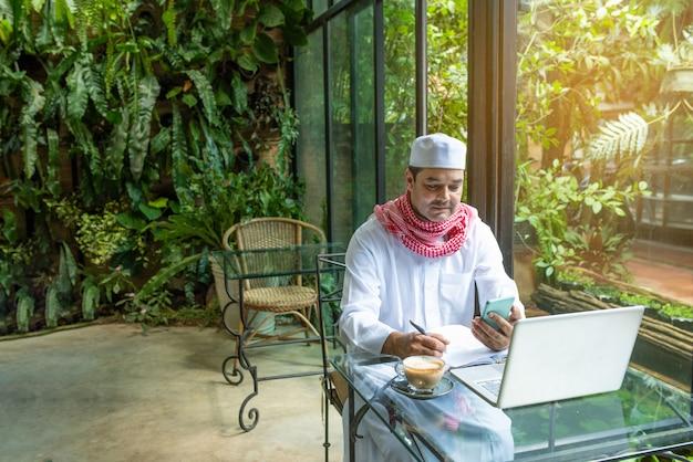 Pakistaanse moslim arabische man hand houden slimme mobiele telefoon en laptop op tafel Premium Foto