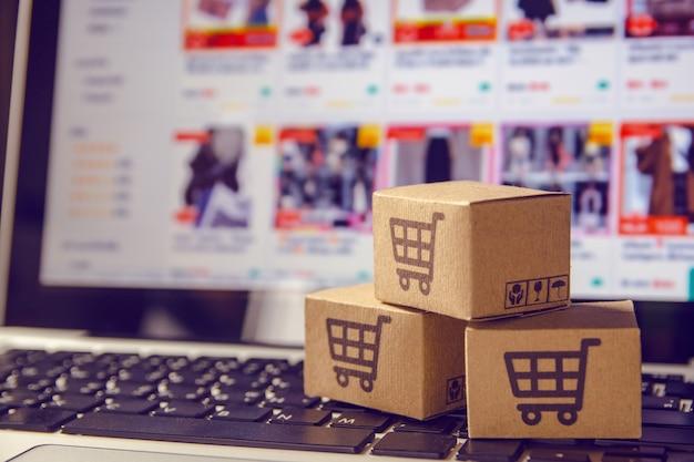 Pakket- of papierdozen met een winkelwagenlogo in een trolley op een laptop toetsenbord Premium Foto