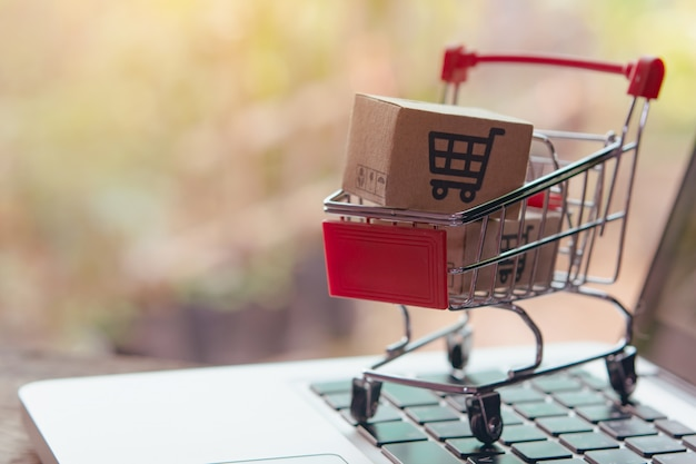 Pakket- of papierdozen met een winkelwagenlogo in een trolley op laptoptoetsenbord. boodschappenservice op het online web. biedt levering aan huis. Premium Foto