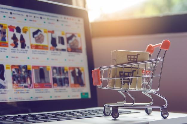 Pakket- of papieren dozen met een winkelwagentje-logo in een trolley op een laptoptoetsenbord. Premium Foto