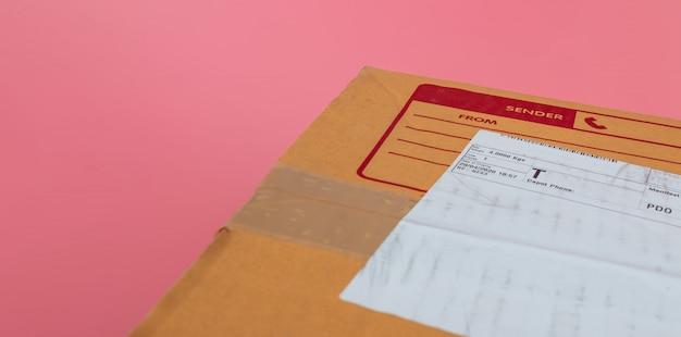 Pakketdozen worden verzonden door rederijen op een felroze achtergrond. Premium Foto