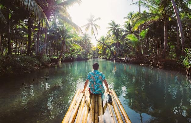 Palmwildernis in de filippijnen. concept over reislust tropische reizen. slingeren op de rivier. mensen hebben plezier Premium Foto