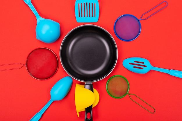 Pan in het midden met kookgerei rond geïsoleerd op rood Premium Foto