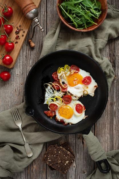 Pan met gebraden eieren en kersentomaten op rustieke lijst. Premium Foto