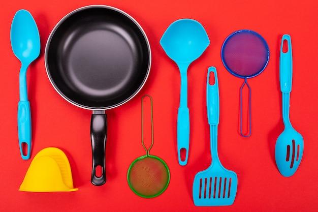 Pan met keukengerei op rood wordt geïsoleerd dat Premium Foto
