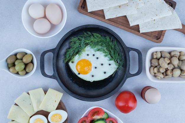Pan met omelet en gekookte eieren, kaas, tomaat, champignons op wit. Gratis Foto