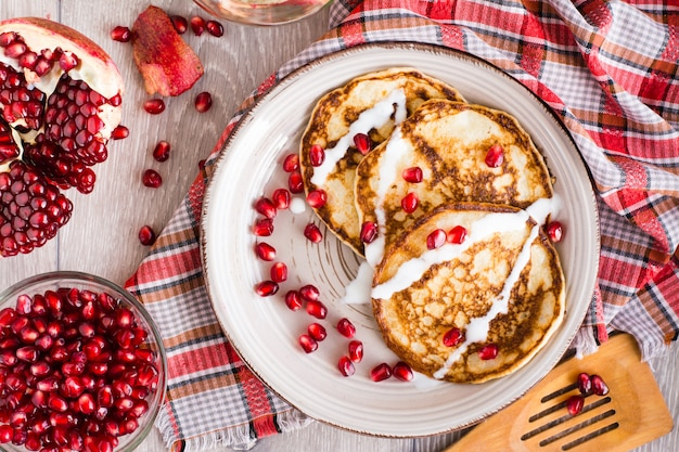 Pannekoeken met zure room en granaatappelzaden op een platein hoogste mening Premium Foto