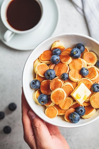 Pannenkoek granen met boter en bessen in een witte kom, bovenaanzicht. ontbijt eten concept. Premium Foto