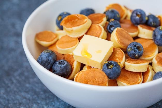 Pannenkoek granen met boter en bessen in een witte kom. ontbijt eten concept. Premium Foto