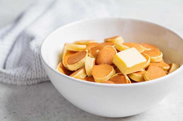 Pannenkoek granen met boter in een witte kom, kleine trend pannenkoeken. ontbijt eten concept. Premium Foto