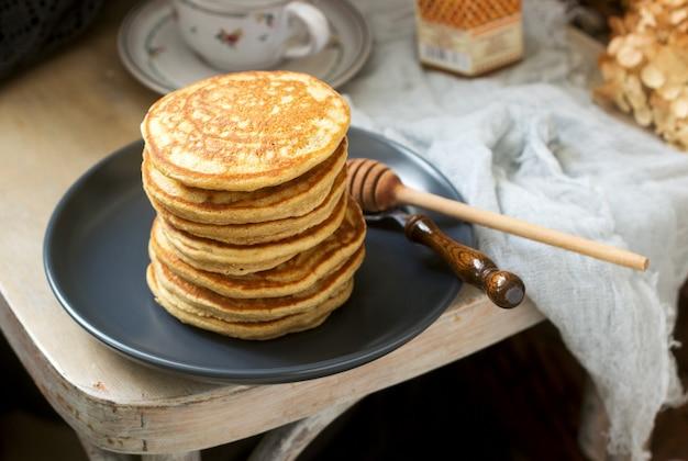 Pannenkoeken met banaan, noten en honing, geserveerd met thee. rustieke stijl. Premium Foto
