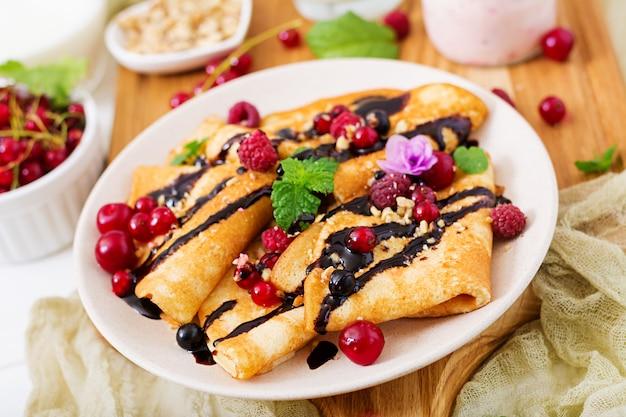 Pannenkoeken met chocolade, honing, noten en zomerbessen. lekker ontbijt Premium Foto