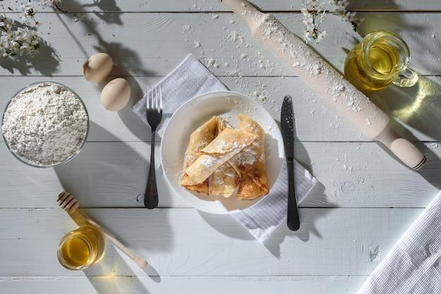 Pannenkoeken met kwark op een witte houten achtergrond. shot met honing, zonnebloempitten, meel en eieren. een traditioneel ontbijt. Premium Foto