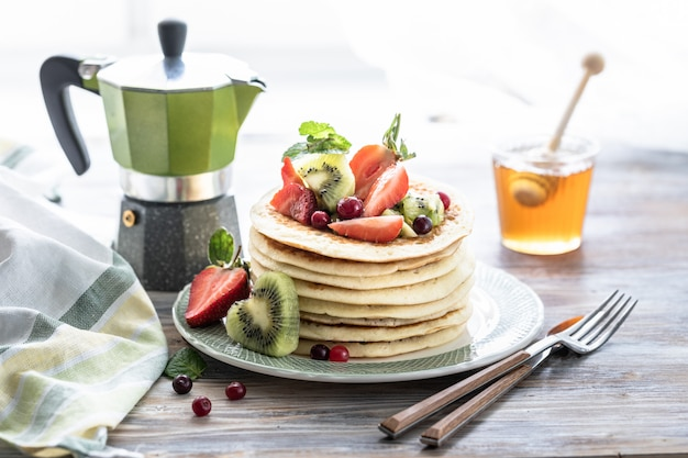 Pannenkoeken met verse bessen van frambozen, krenten, bosbessen, met honing en thee Premium Foto