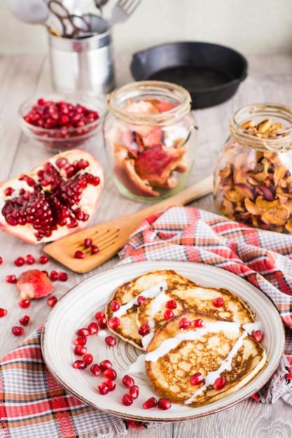 Pannenkoeken met zure room en granaatappelzaden op een plaat Premium Foto