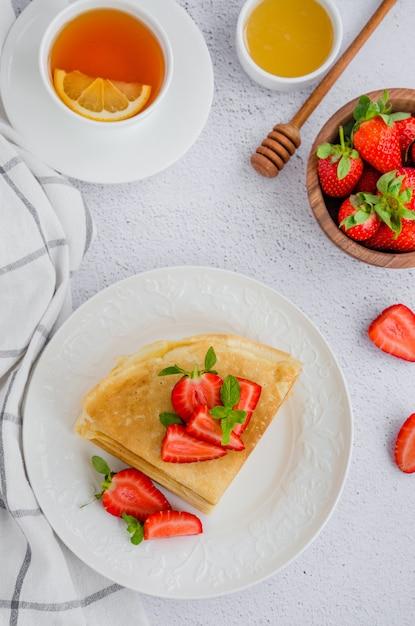 Pannenkoeken, traditionele russische dunne pannenkoeken op een witte plaat met verse aardbeien en honing op een lichte achtergrond. russische maslenitsa. verticale oriëntatie. bovenaanzicht Premium Foto