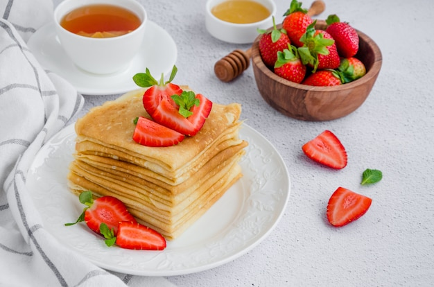 Pannenkoeken, traditionele russische dunne pannenkoeken op een witte plaat met verse aardbeien en honing op een lichte achtergrond. Premium Foto
