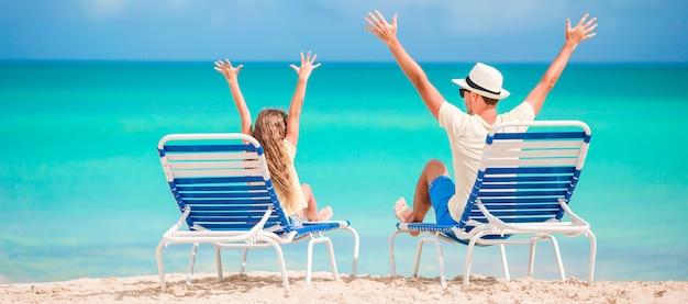 Panorama van familie van vader en kind handen omhoog op strand zittend op chaise-longue Premium Foto