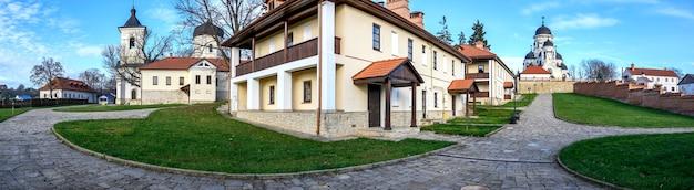 Panorama van het capriana-klooster. zichtbare winter- en stenen kerken. kale bomen, groene gazons en gebouwen, mooi weer in moldavië Gratis Foto
