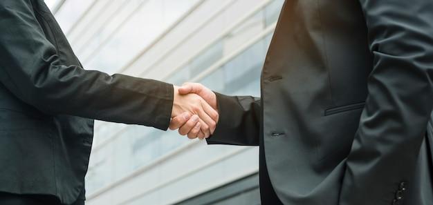 Panorama van onderneemster en zakenman het schudden handen Gratis Foto
