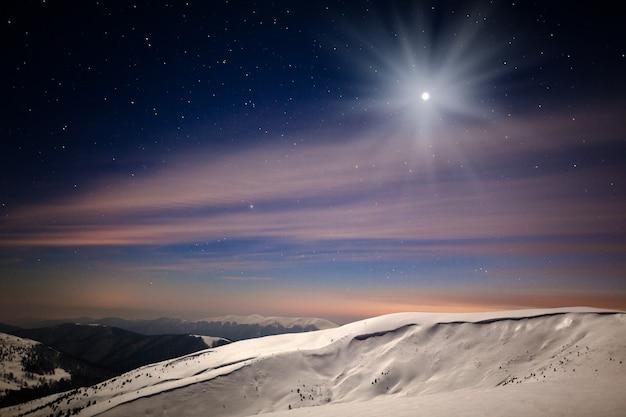 Panoramisch nachtzicht van winter bergdal bedekt met sneeuw, bergen en maan van boven op winternacht met veel sterren aan de hemel Premium Foto