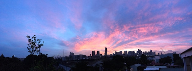 Panoramisch schot van de stadsbouw onder een purpere en blauwe hemel Gratis Foto