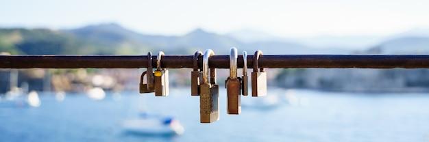 Panoramisch zicht op roestige sloten op een reling aan de kust in een zonnige dag Premium Foto