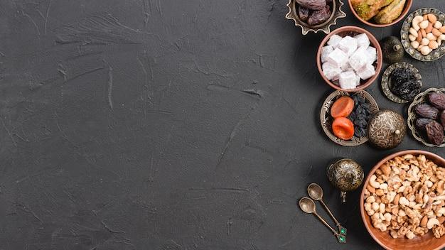 Panoramisch zicht op witte lukum; noten en gedroogde vruchten voor ramadan festival op zwarte concrete achtergrond Gratis Foto
