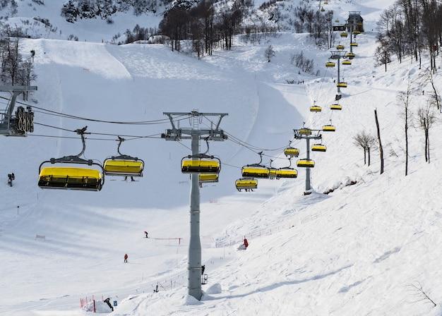 Panoramisch zicht van stoeltjeslift op skihellingen en berg achtergrond in rosa khutor alpine resort. sochi, rusland Premium Foto