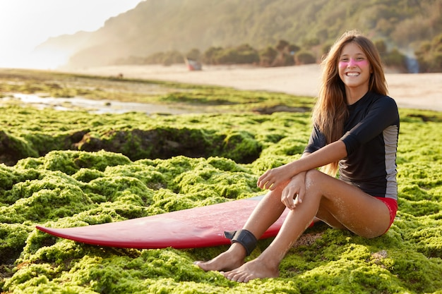Panoramisch zicht van vrij lachende vrouwelijke surfer voelt zich veilig als surfplankriem gebruikt Gratis Foto