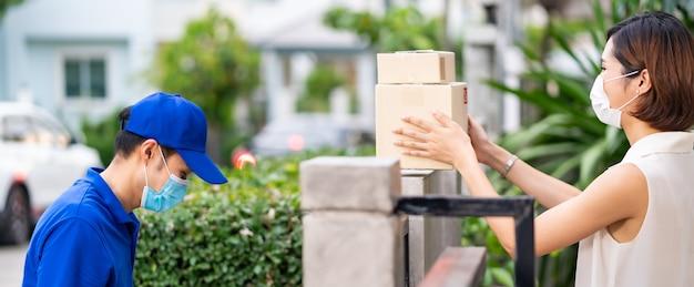 Panoramisch zijaanzicht aziatische vrouw met gezichtsmasker klant neemt contactloze winkelpakketten Premium Foto