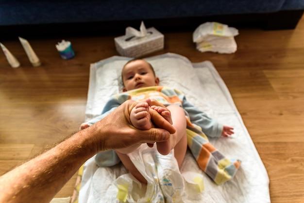 Papa die de voeten van een baby houdt terwijl het veranderen van zijn luier. Premium Foto