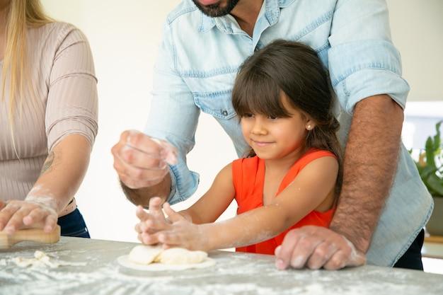 Papa die dochter toont hoe deeg op keukentafel met rommelige bloem te maken. jong stel en hun meisje die broodjes of pastei samen bakken. familie koken concept Gratis Foto