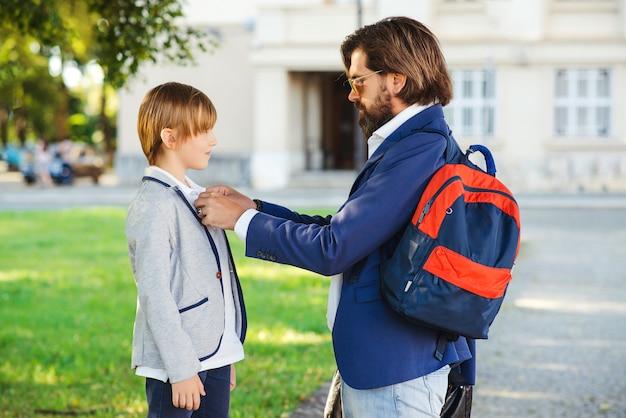 Papa geeft steun aan zijn zoon voor het beginnen met school. Premium Foto
