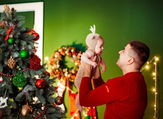 Papa houdt dochtertje in een hert pak poseren voor een kerstboom Gratis Foto